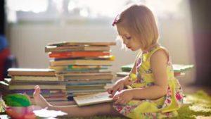 241565-little-girl-reading-stacks-of-books-early-childhood-literacy-childrens-books