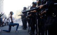 Η φωτογραφία που ανατριχιάζει – Μαύρη διαδηλώτρια γονατίζει μπροστά στους αστυνομικούς